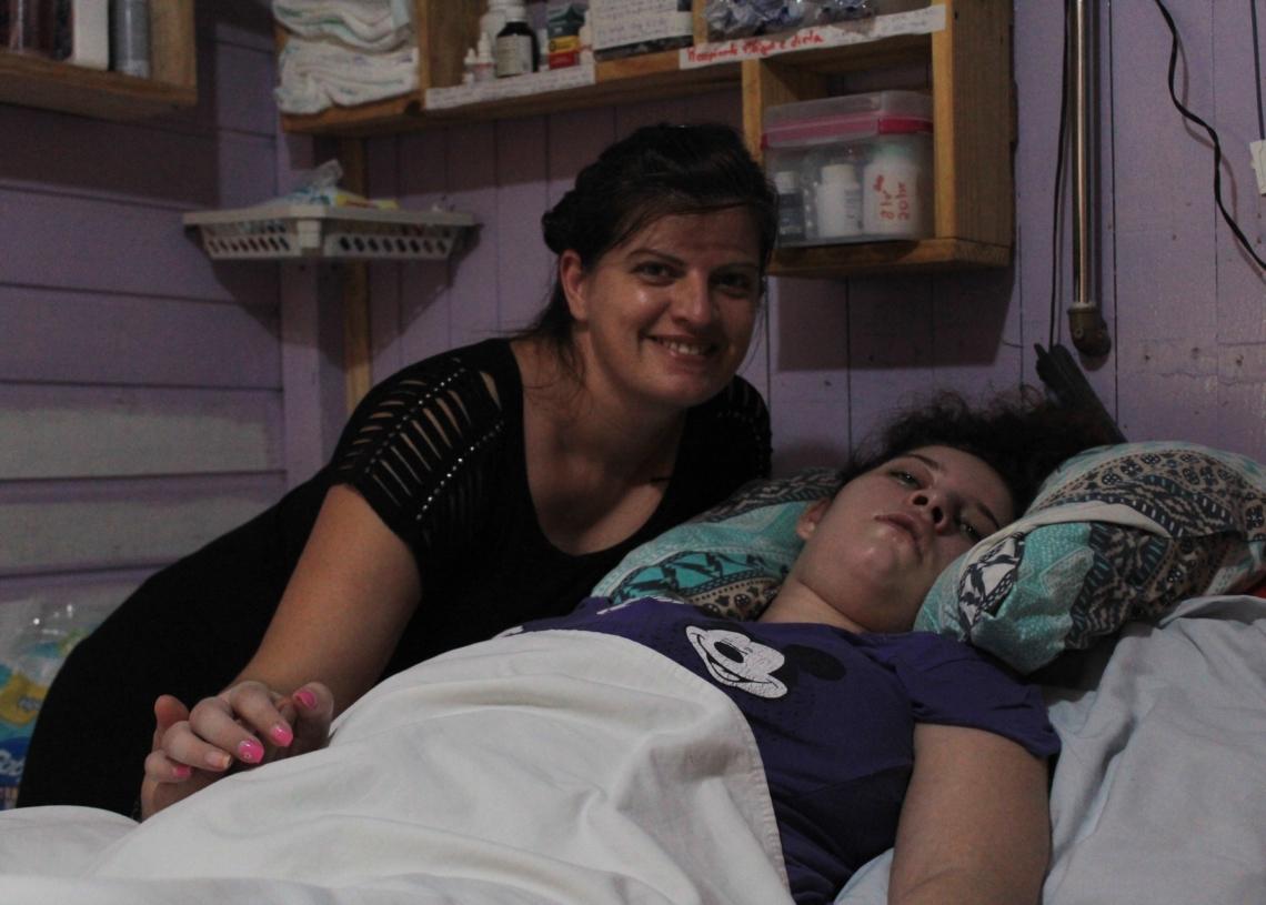Laci e Jenifer no quarto da jovem, que está acamada  Foto: Lilian Moraes