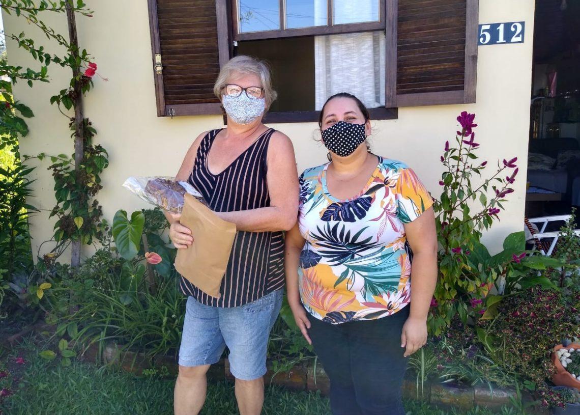 Educadora social Elissiane entregando kit de materiais a serem utilizados nas atividades da semana Fotos: Divulgação